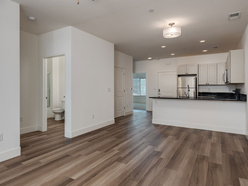 Photo of a vacant unit shows dark wood floors, an open concept kitchen, and a brief view into the restroom